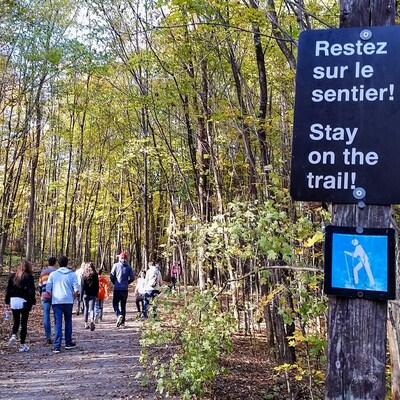 Des randonneurs dans le parc de la Gatineau, à l'automne. Sur une affiche, on peut lire : « Restez sur le sentier! » (Archives)