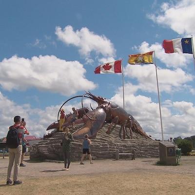 Des touristes se prennent en photo devant le homard géant, à Shediac.