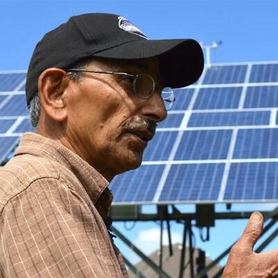 Shiv Chopra est devant des panneaux solaires