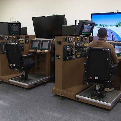 Un homme devant une console et un écran qui simulent la conduite d'une locomotive