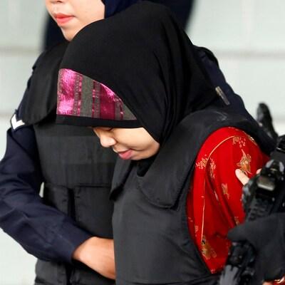 Siti Aisyah est escortée par deux policières. Elle porte un voile et un gilet pare-balles.
