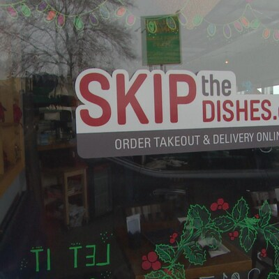 La vitrine d'un magasin avec un autocollant «Skip the dishes».