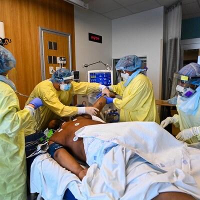 Un homme sur une civière entouré de quatre membres du personnel d'un hôpital.