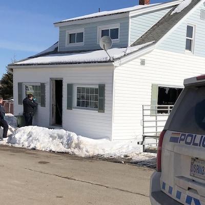 Deux policiers examinent la maison où deux corps ont été trouvés
