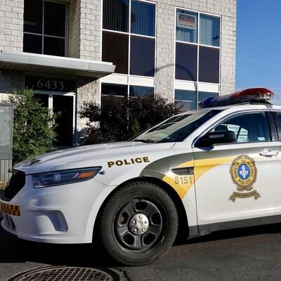 Une voiture de police devant un immeuble.