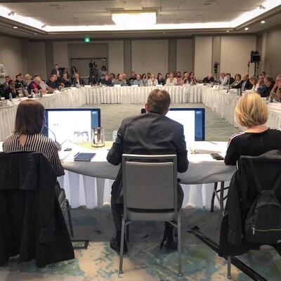 Des dizaines d'intervenants autour d'une grande table.