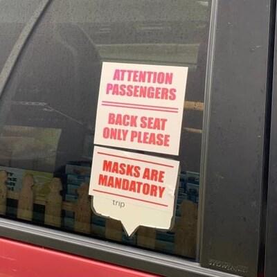 Une pancarte collée sur un texte indique que les masques sont obligatoires.
