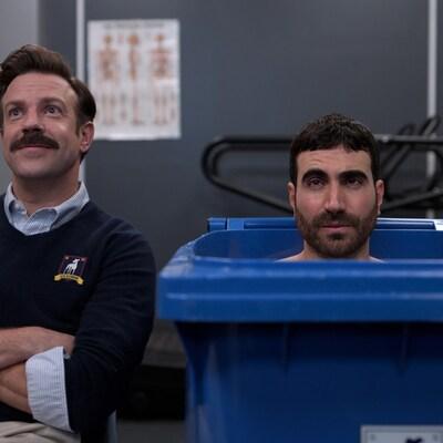 Deux hommes sont assis, dont l'un dans un bac de recyclage.