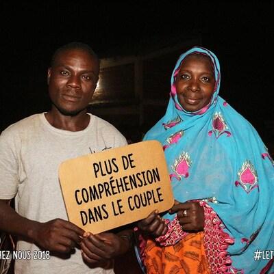 Un homme et une femme tiennent une pancarte : Plus de compréhension dans le couple.