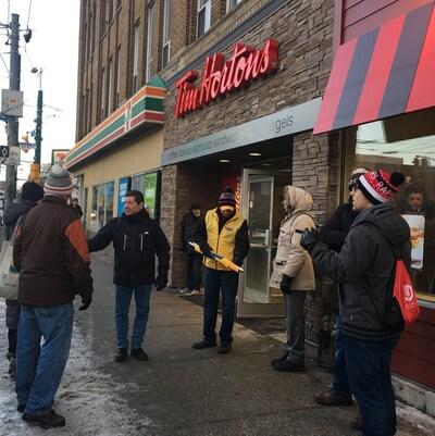 Photo de personnes vêtues de manteaux se tenant à l'entrée d'un Tim Hortons.