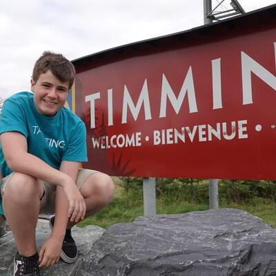 Une fille et un gars devant la pancarte de la ville de Timmins.