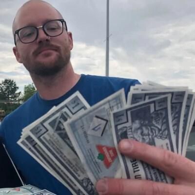 Un homme montre sa grande quantité d'argent Canadian Tire.
