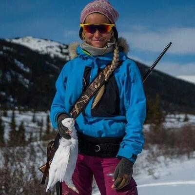 Une femme debout dans la neige avec un oiseau blanc dans la main.