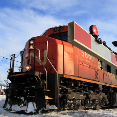 Une locomotive traverse un passage à niveau.