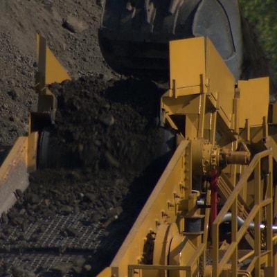 Un convoyeur reçoit des sols contaminés déposés par une grue.