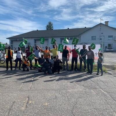 Des travailleurs manifestent avec une pancarte.