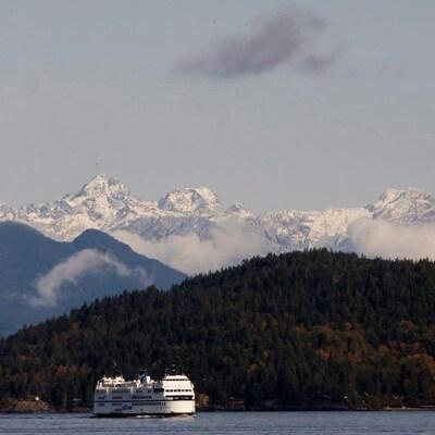 Un traversier de BC Ferries vogue en mer près de Vancouver, des montagnes de conifères et des montagnes enneigées à l'arrière-scène.