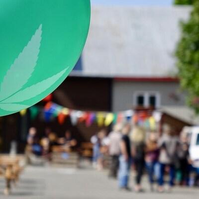 Un ballon vert avec une feuille de marijuana, avec des festivités en arrière-plant