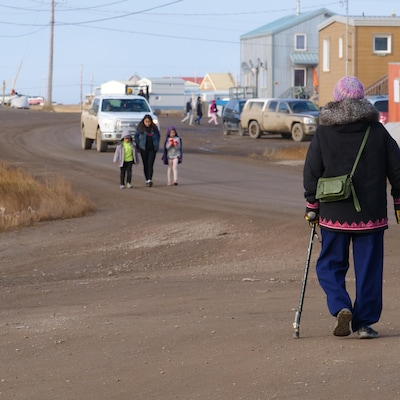 Une femme marche à l'aide d'une canne dans une rue de Tuktoyaktuk.