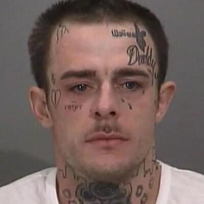Une photo d'un homme blanc avec des tatouages sur le visage et le cou.