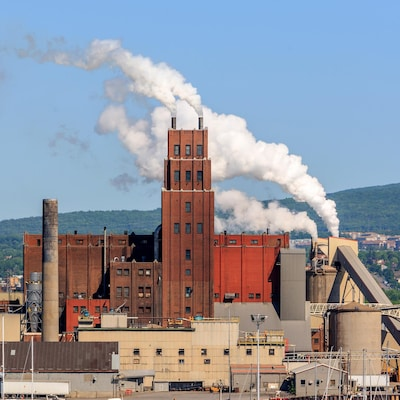 Une usine dont les cheminées dégagent de la fumée. Au loin, on aperçoit la ville.