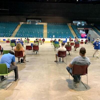 Des personnes assises sur des chaises à l'intérieur du Colisée de Moncton semblent en attente.