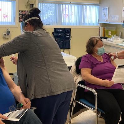 Des gens se font vacciner assis sur une chaise.