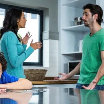 Un homme et une femme discutent debout et un enfant se trouve à l'écart.