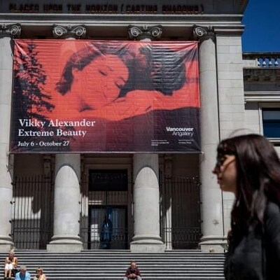 Une femme marche devant le musée des beaux-arts de Vancouver.