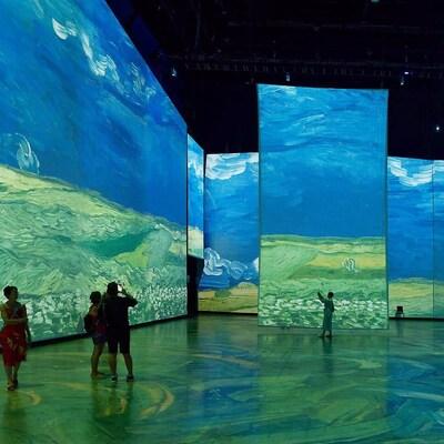Des personnes observent des images de toiles de Van Gogh projetées sur d'immenses écrans dans une grande salle d'exposition intérieure.