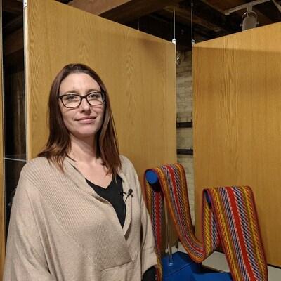 Vania Gagnon pose devant la ceinture fléchée exposée dans une vitrine du musée.