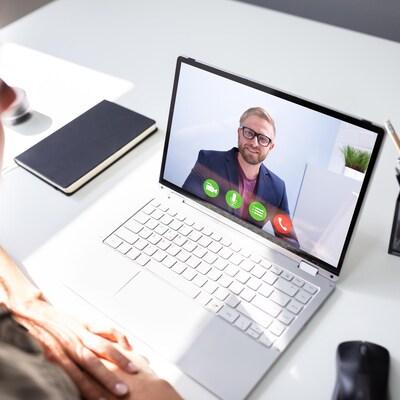 Une femme en appel vidéo avec un homme, sur son ordinateur.