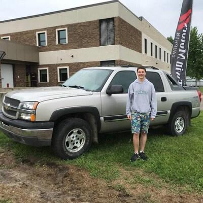 Un adolescent devant un camion gris.