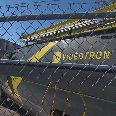 Des camions de Vidéotron sont stationnés derrière une clôture.