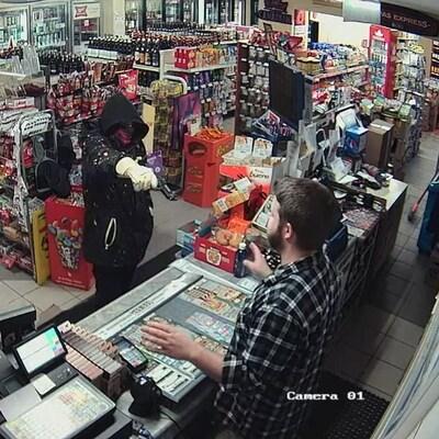 Dans un dépanneur, un homme cagoulé dans un dépanneur pointe une arme à feu en direction.