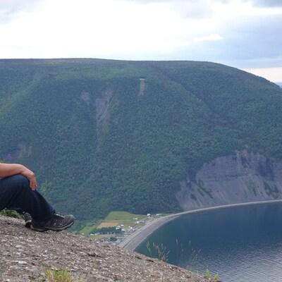 Assis au sommet du mont Saint-Pierre, un homme regarde les sommets et une baie du fleuve Saint-Laurent.