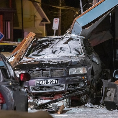 Un véhicule noir sous un balcon effondré, dans la nuit