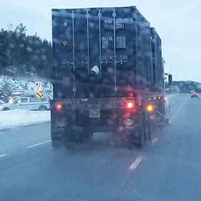 L'homme assis à l'arrière du camion-remorque