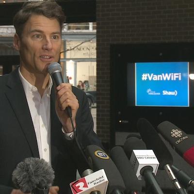 Le maire de Vancouver tenant un micro