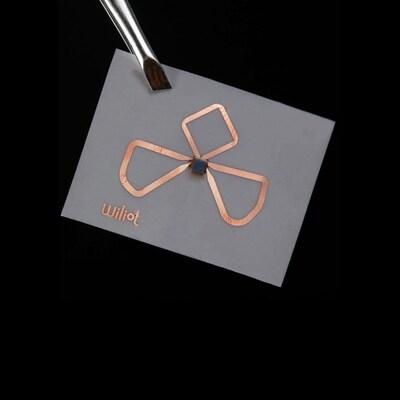 Une photo montrant une puce Wiliot tenue par une pince à sourcils. La puce est un minuscule carré collé à un bout de papier gris et entouré de trois antennes en cuivre en forme de pétales de fleur.