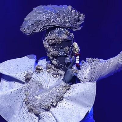 Une capture d'écran montrant une personne masquée portant un chapeau en forme d'huître et un costume gris.