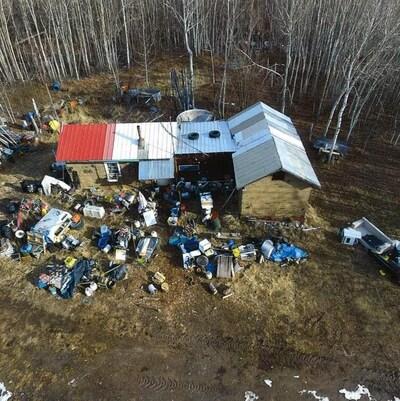 Propriété vue du haut des air montrant une cabane et beaucoup d'objets éparpillés.