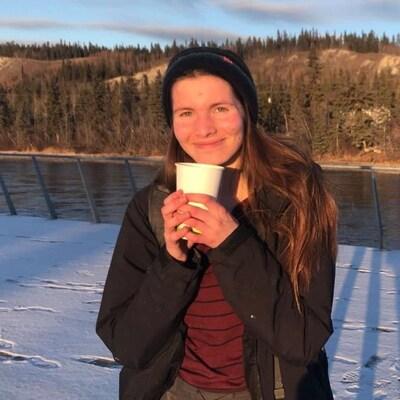 Une jeune femme tient un gobelet en plastique dans les mains. Elle pose devant une rivière. Il y a des arbres de l'autre côté de la rive.
