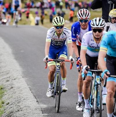Il grimace sous l'effort, à l'avant d'un groupe de cyclistes.