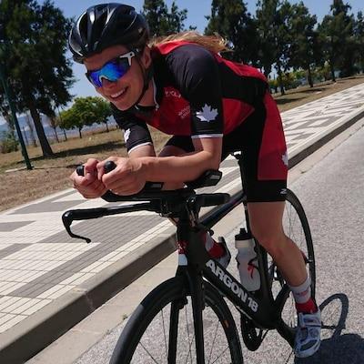Jeune femme souriante, sur un vélo.
