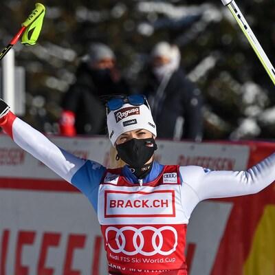 Une skieuse lève les bras au ciel.