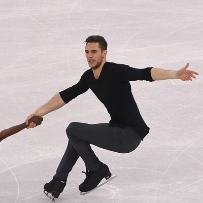 Il réalise une figure sur la patinoire.