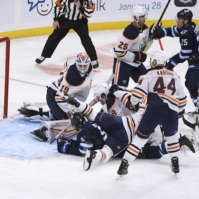La rondelle glisse derrière le gardien sous le regard de quatre joueurs des Oilers.