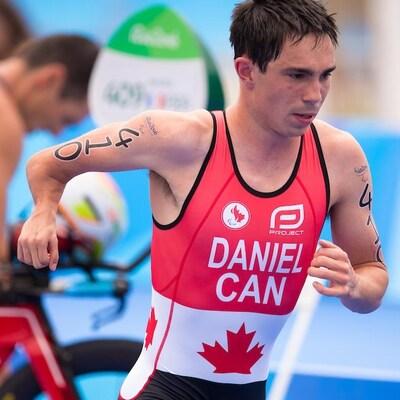 Stefan Daniel court en combinaison durant un para triathlon.