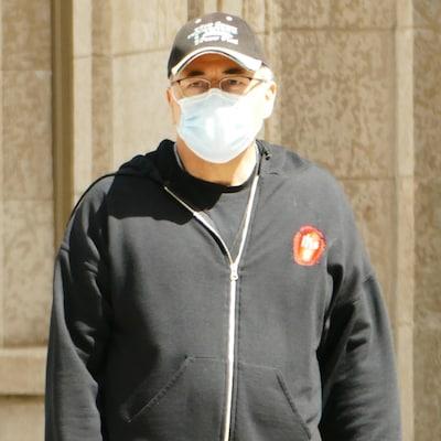 Un homme porte un masque.